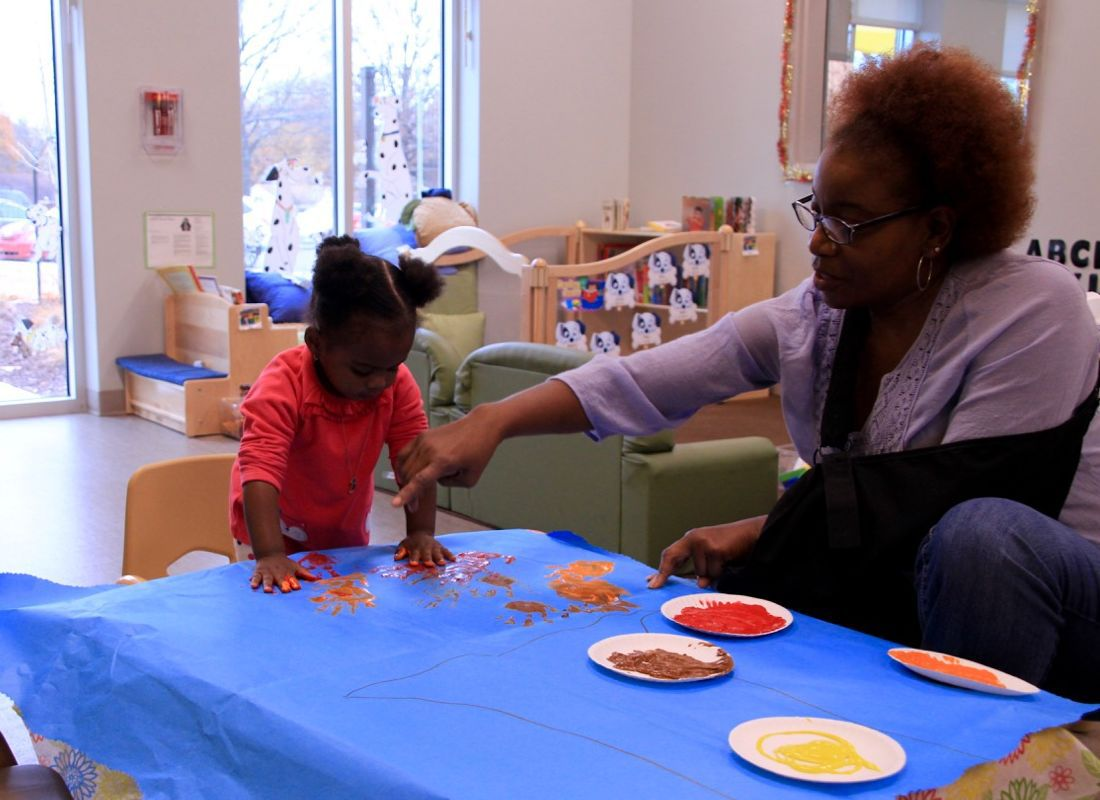 """Owens works on vocabulary and motor skills with her students while creating a """"handprint"""" tree."""