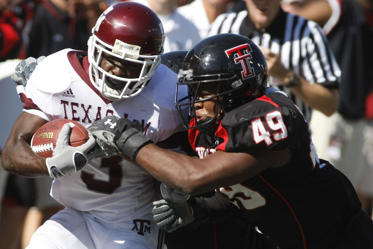 Texas A&M's Mike Goodson (3) is stopped by Texas Tech's Joe