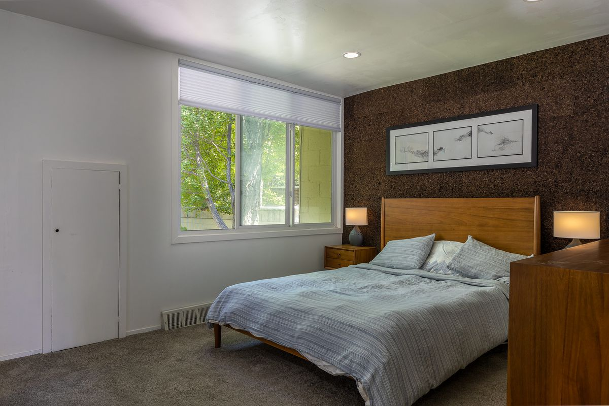 A bedroom has a wooden bed, cork accent wall, and large window.