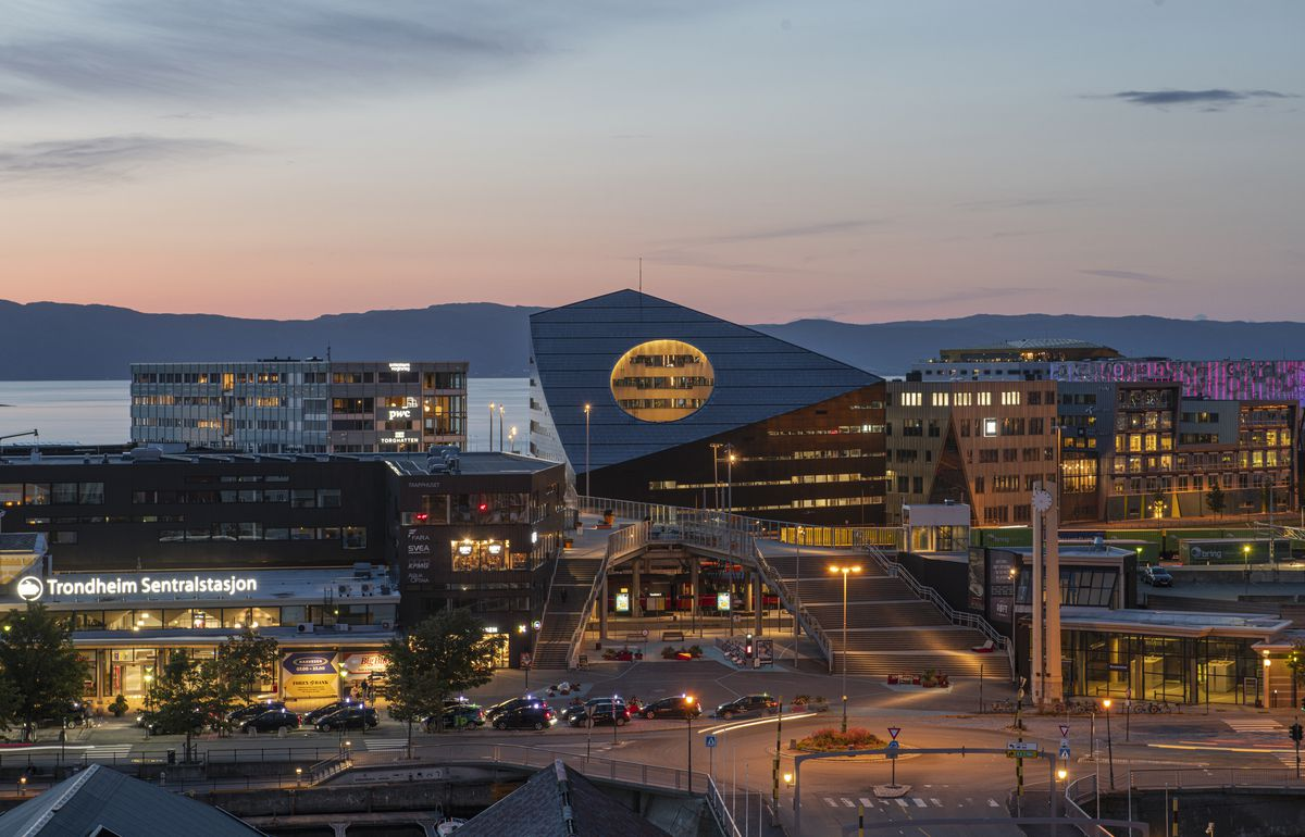 An angular office building sits among a cityscape at dusk. The building features a circular cutout on its slanted roof, carving out vistas for spaces within.