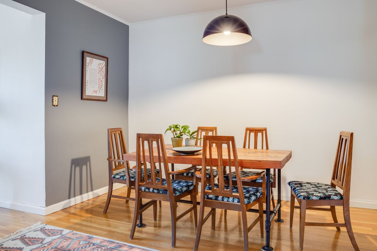 A dining area with grey walls, a wooden table, and several chairs.
