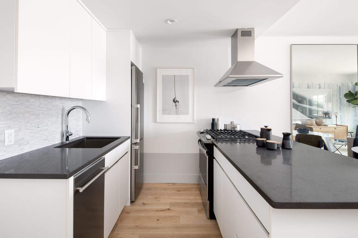 A kitchen with an island and white cabinetry.