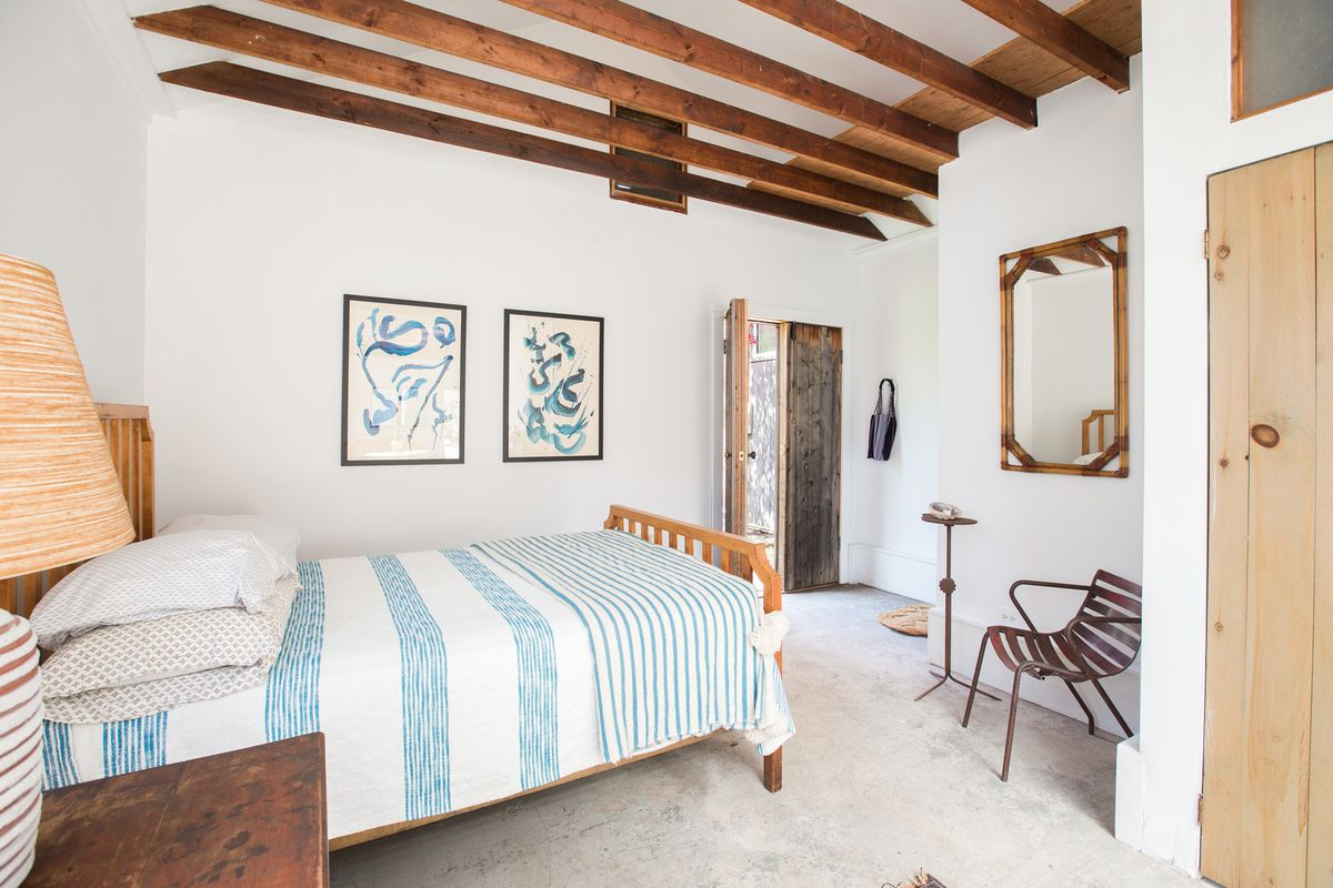 A bedroom area has a white and blue bed, light colored floors, and exposed wooden beams.