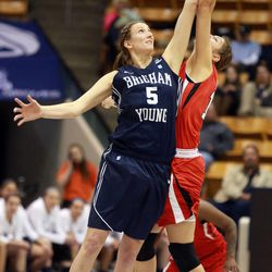 BYU's Jennifer Hamson and Utah's Emily Potter reach for the ball at the start of the first overtime period of a women's basketball game at the Marriott Center in Provo on Saturday, Dec. 14, 2013. Utah won in double overtime 82-74.