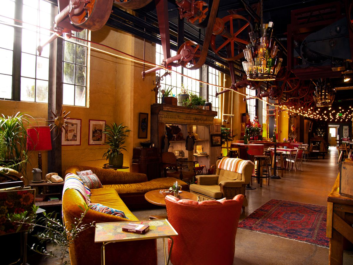 Sunlight pours into a large industrial room with large warehouse windows. Eclectic furniture in warm tones are arranged to support groups and a jewel-toned rug is on the cement ground to help warm the space.