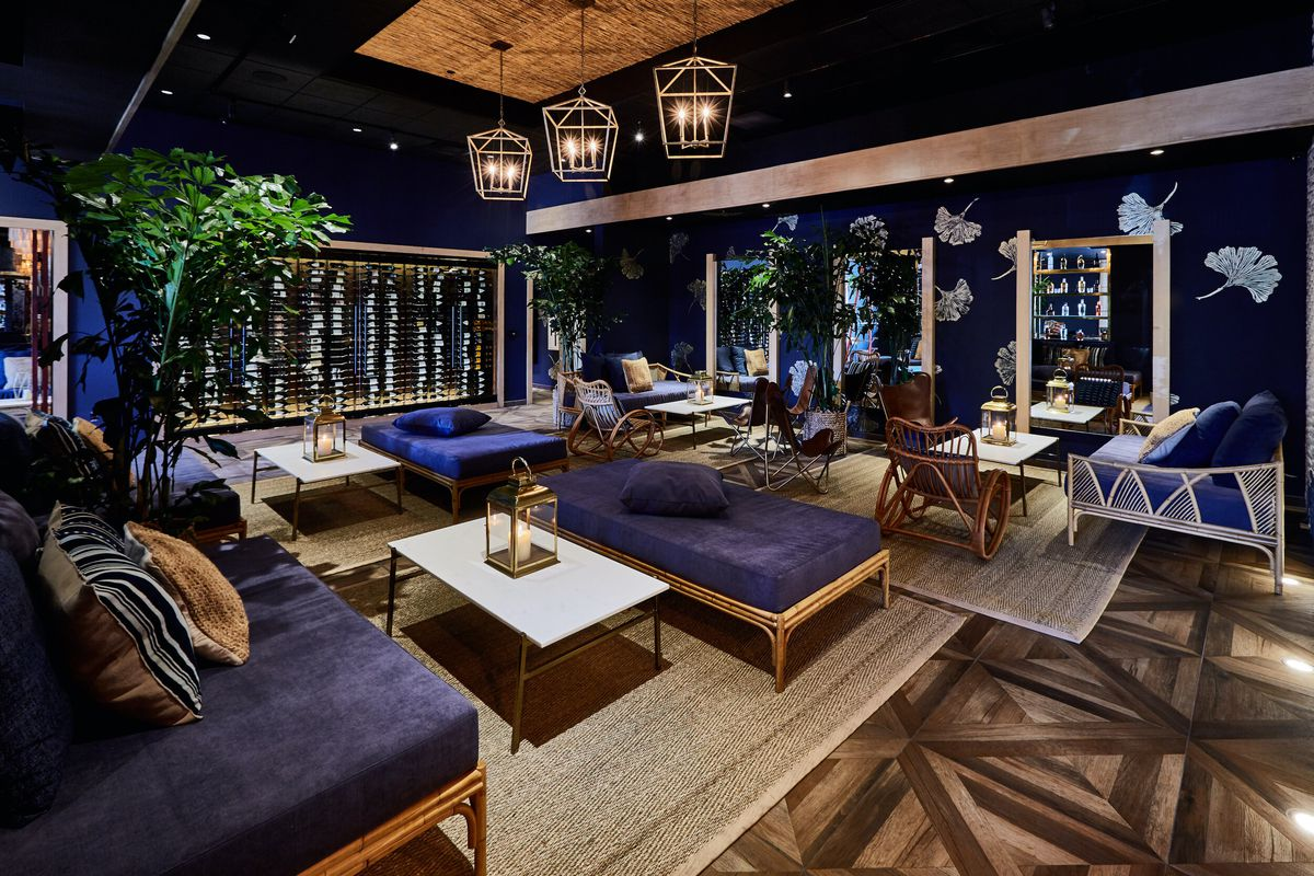 A deep blue and dimly lit cocktail bar with lush decor and lots of gold accents.