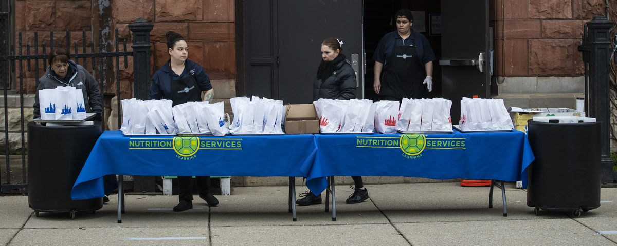 Lunchroom workers hand out three days of free breakfast and lunch meals for students at William P. Nixon Elementary School, 2121 N. Keeler Ave., Thursday morning. All Illinois schools, including Chicago Public Schools, are closed for weeks amid fears of the coronavirus pandemic.