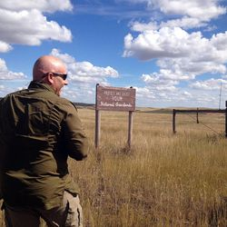 """Ed Arnett with the Theodore Roosevelt Conservation Partnership notes the oil extraction occurring against the backdrop of a """"protect public lands"""" sign in western North Dakota. He says energy development of natural resources and conservation can be accomplished in a """"winning balance."""""""