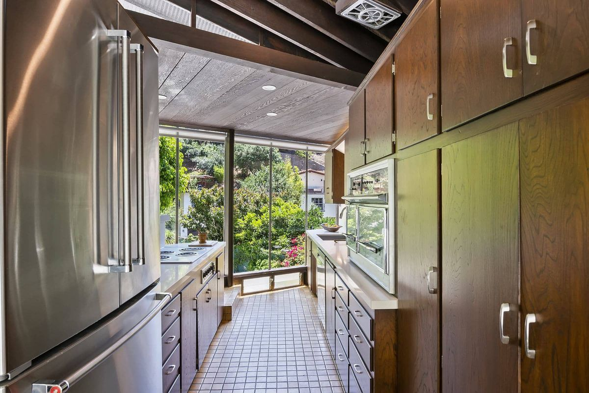 A view down a kitchen with stainless steel appliances and wooden cabinets.