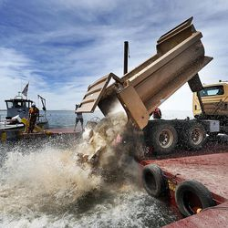 A truck dumps boulders in the water at Willard Bay on Thursday, June 9, 2016. The Utah Division of Wildlife Resources used a barge and dump trucks to place boulders in Willard Bay to enhance fish habitat.