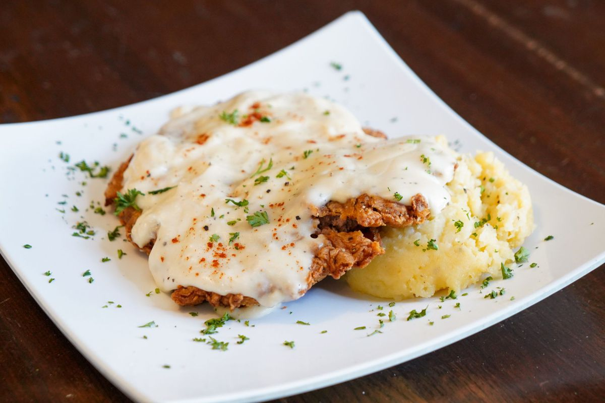 A chicken fried steak topped with gravy and served with a side of mashed potatoes.