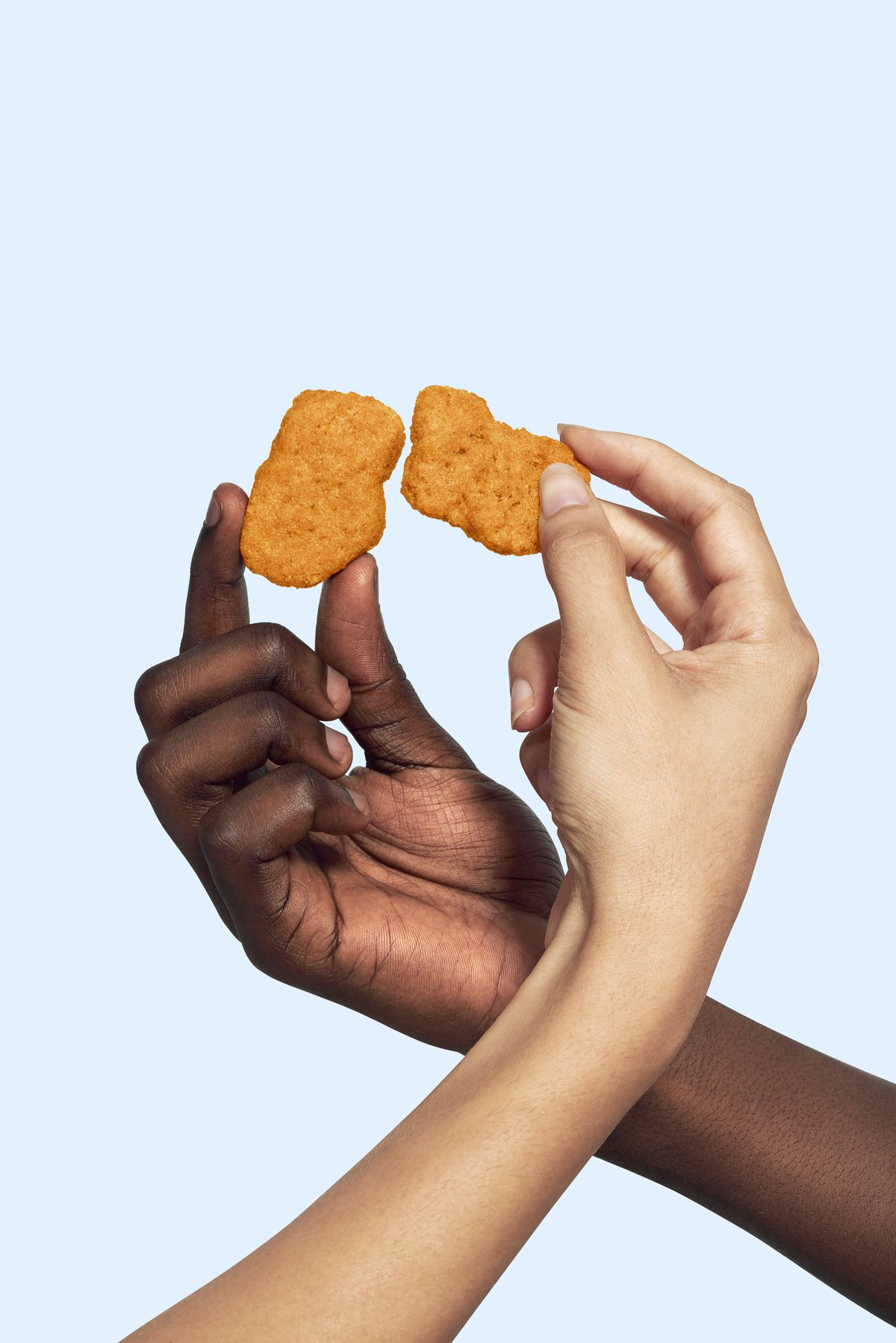 The hands of two people, crossed at the wrists, holding nuggets that are almost touching.
