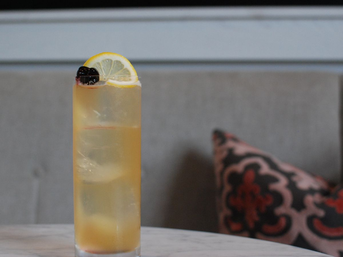 A tall glass with an effervescent beverage garnished with a lemon wheel
