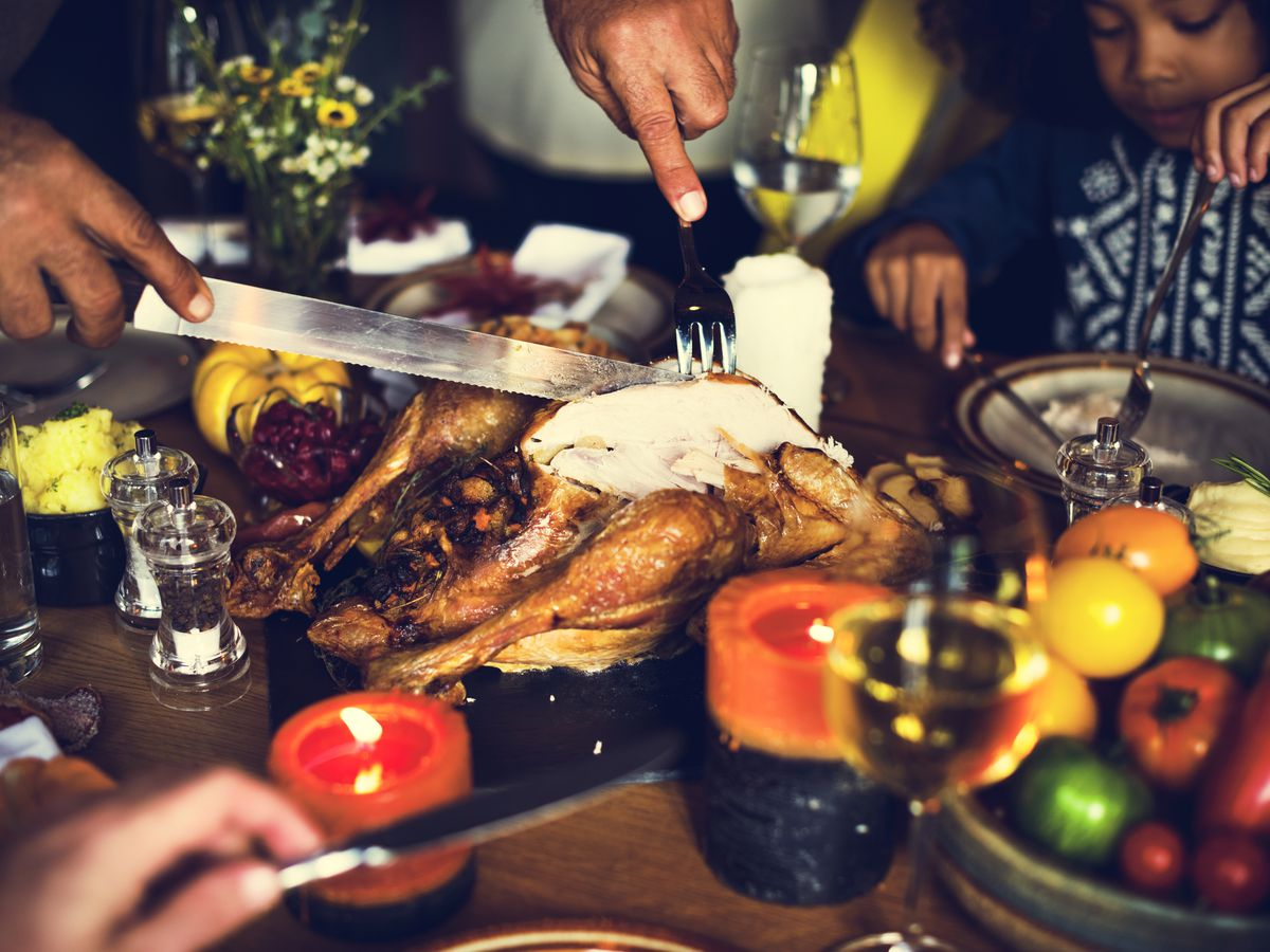 A man's black hands use a knife and fork to carve into a turkey on a decorated Thanksgiving table as a little girl eats turkey off her plate.