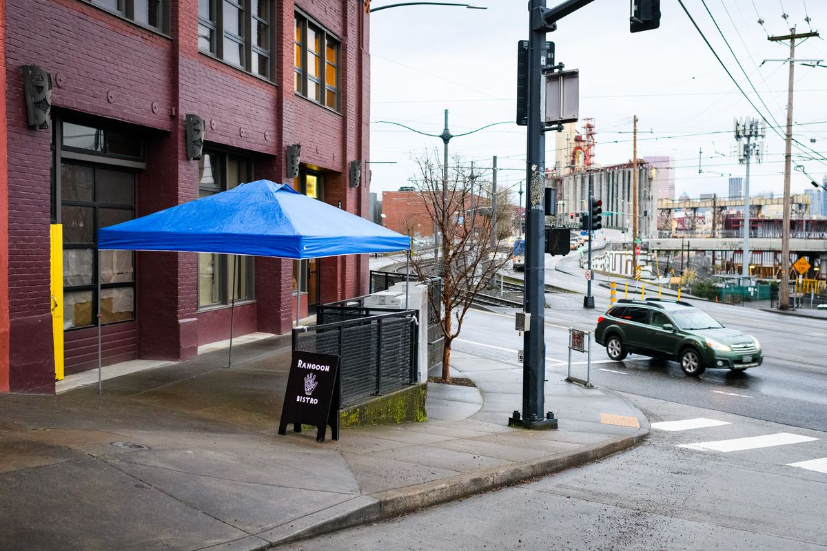"""A blue tent covers a chunk of patio next to a sandwich board that reads """"Rangoon Bistro."""""""