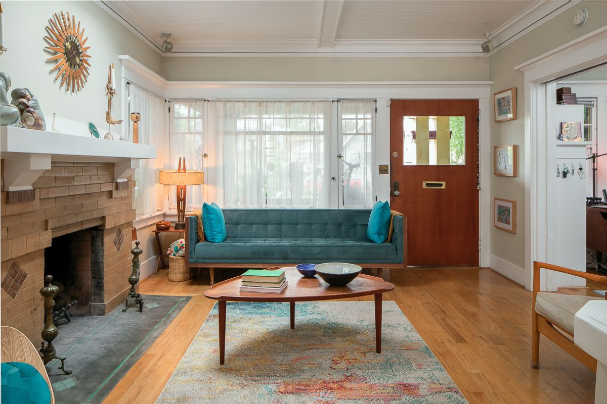 A room with white walls and a fireplace. A blue sofa sits in front of a panel of windows
