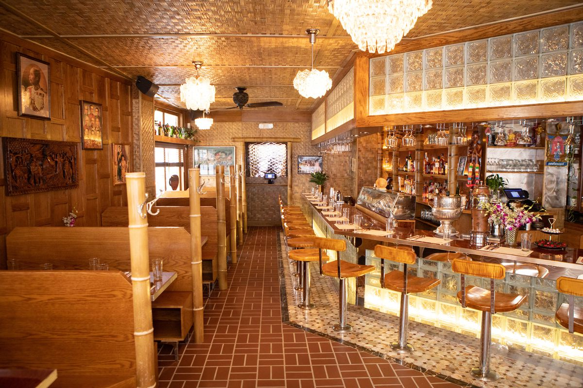 Inside a restaurant with several bar stools on one side and wooden benches on the other