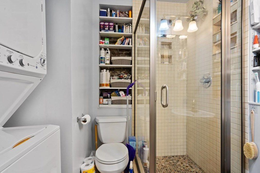 A bathroom with shower with a door next to the toilet, and there's washer-dryer on the other side of the toilet.