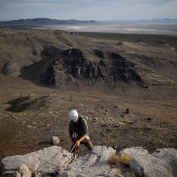 Hawkwatch International research associate Dustin Maloney prepared to rappel at a golden eagle nest site in Tooele County on Friday, June 18, 2021. Maloney found that both of the nestlings had died, and the nest was crawling with parasites.