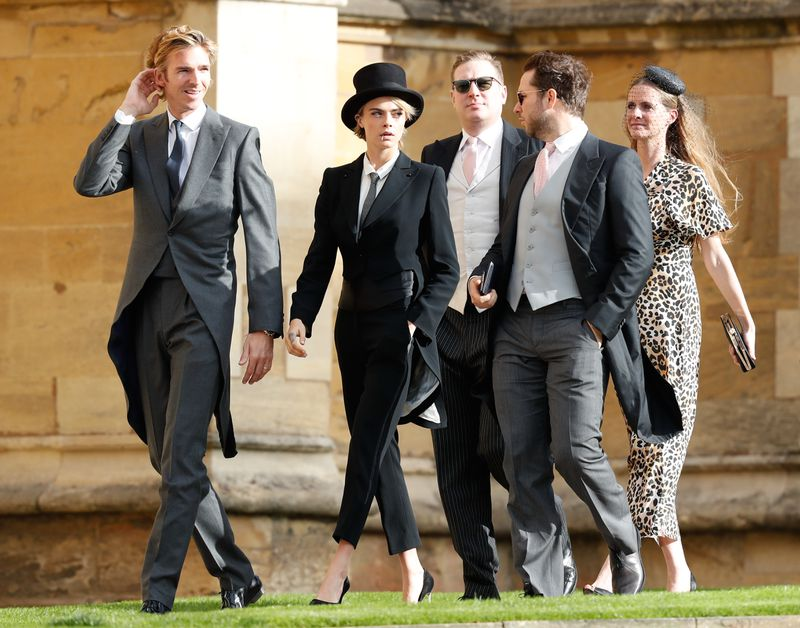 Delevingne wears a top hat, a tuxedo, and high heels.