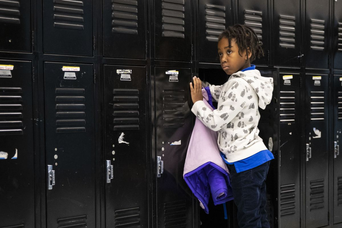 A student puts her coat in her locker at Roswell B. Mason Elementary School on the Southwest Side.