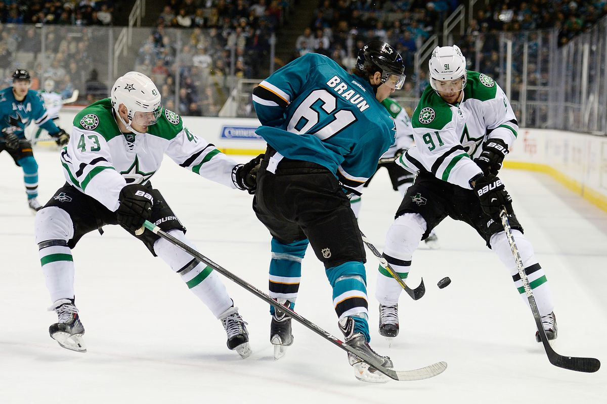 SAN JOSE, CA - DECEMBER 21: Justin Braun #61 of the San Jose Sharks clears the puck past Valeri Nichushkin #43 and through the legs of Tyler Seguin #91 of the Dallas Stars during the first period at SAP Center on December 21, 2013 in San Jose, California.