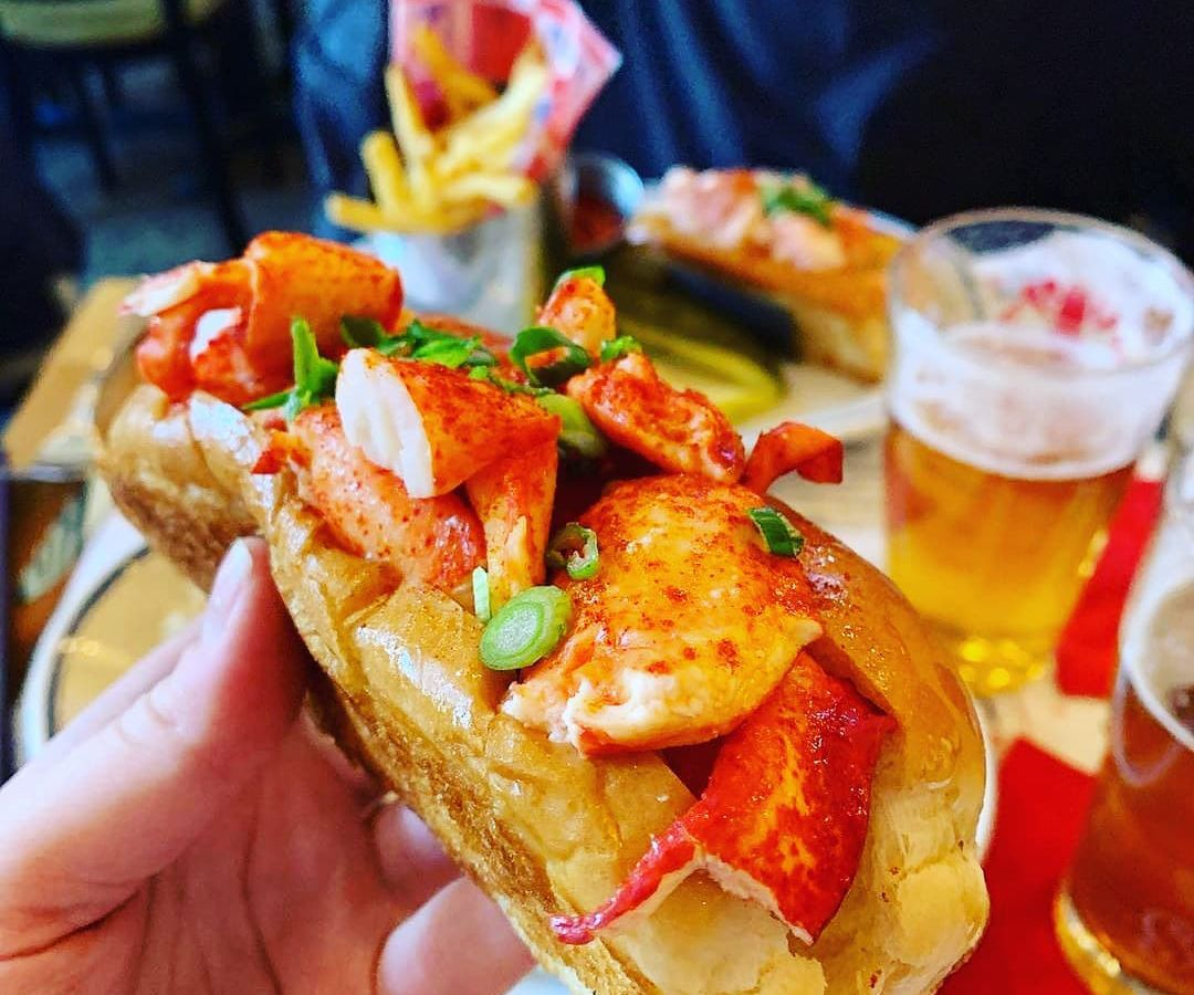 Woman's hand holding a fresh lobster roll
