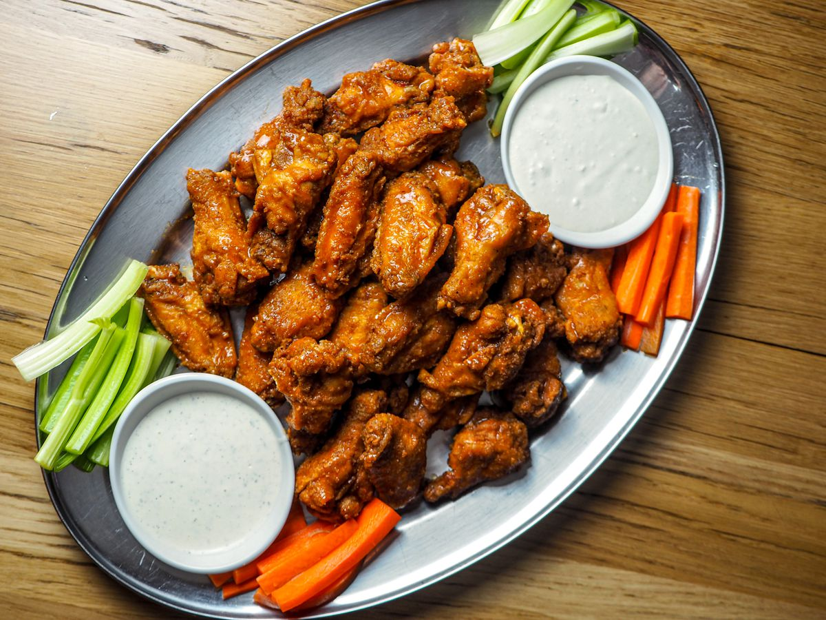 A plate of Buffalo wings with celery and carrots and ramekins of ranch dressing.