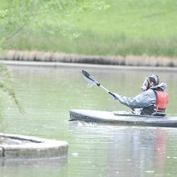 A kayaker in hazmat gear paddles to the island in Liberty Park's pond to move the birds away from the oil spill on Saturday.