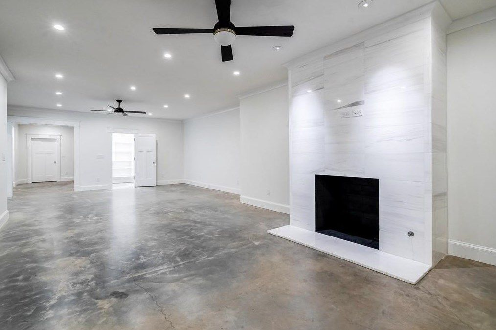 A huge white basement area with concrete floors.