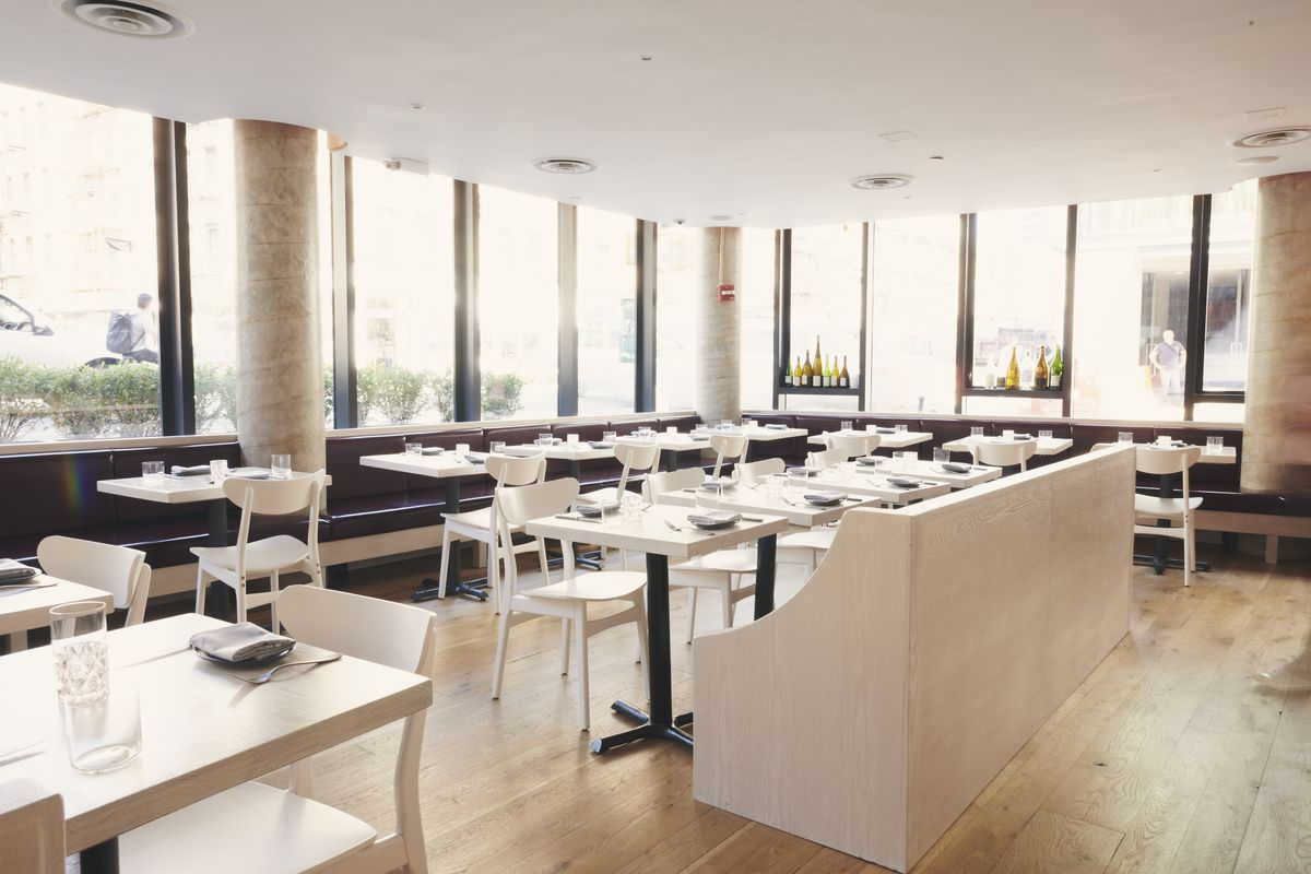 The interior of a restaurant with floor to ceiling windows, off white tables and tables and chairs, and a low ceiling