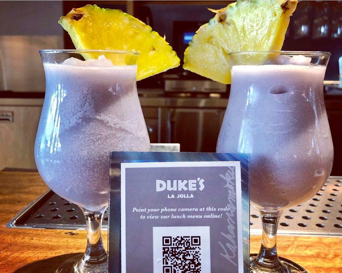 Two blended drinks garnished with pineapple at Duke's La Jolla.