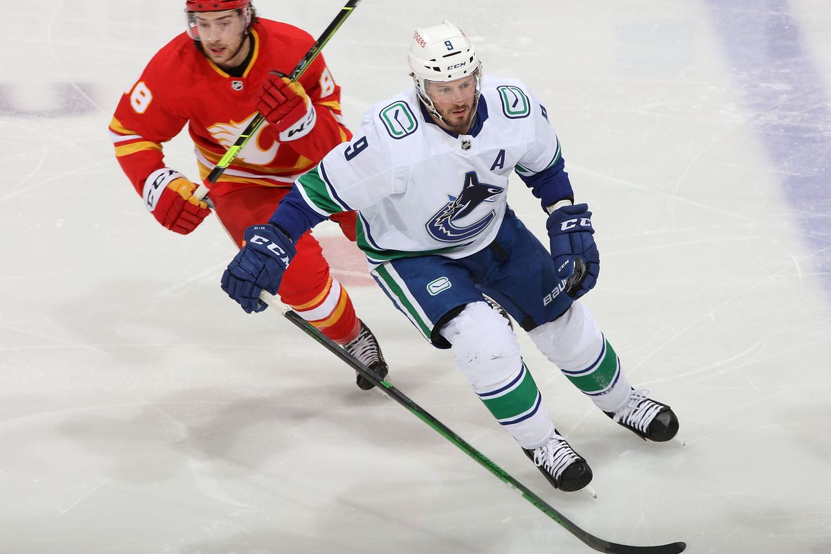 J.T. Miller #9 of the Vancouver Canucks skates against Andrew Mangiapane #88 of the Calgary Flames at Scotiabank Saddledome on May 19, 2021 in Calgary, Alberta, Canada.