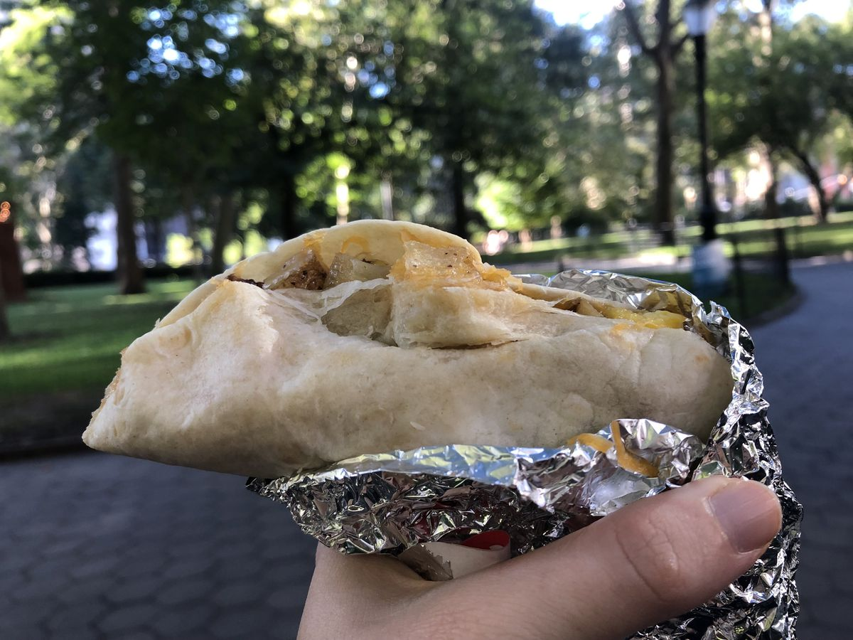 A hand holds a breakfast taco half-wrapped in foil with a view of Madison Square Park in the background.
