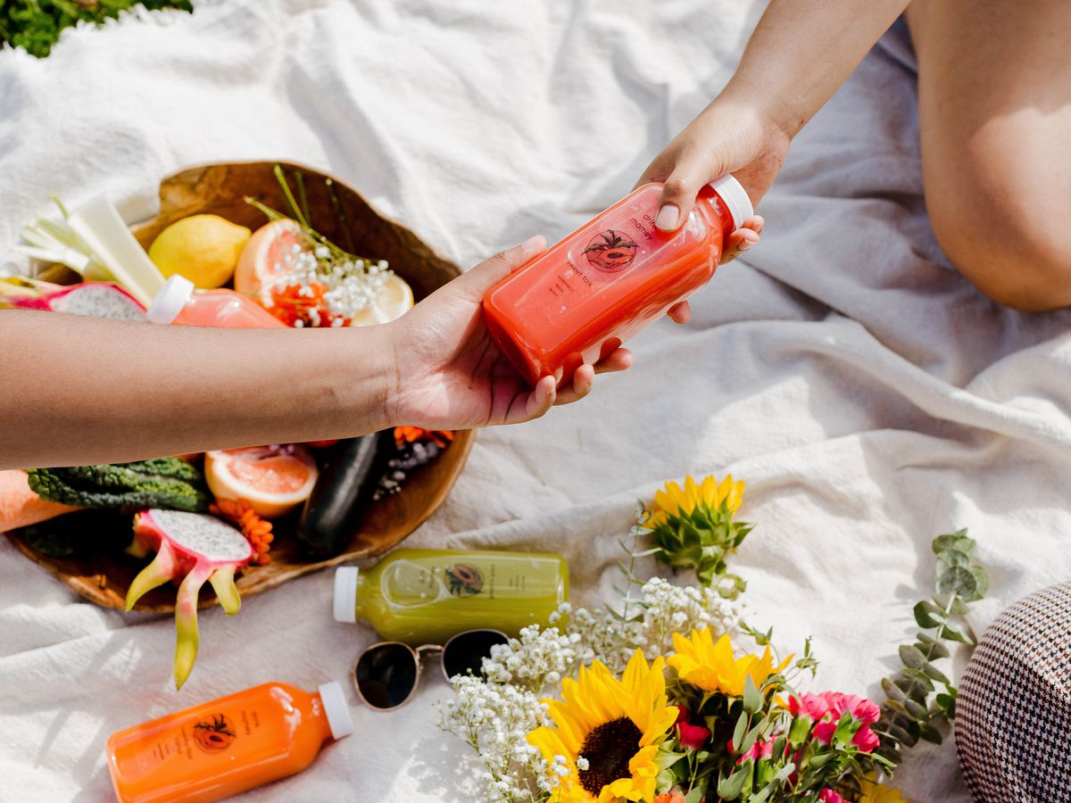 Drink Mamey juices are handed between two people sitting on a blanket at a picnic