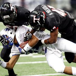Bingham running back Harvey Langi is brought down by Trinity's Sam Smith, left, and teammate Sione Moeakiola as the Miners play Euless (Texas) Trinity Monday in the Kirk Herbstreit Varsity Football Series at Dallas Cowboys Stadium in Arlington, Texas. Trinity won 42-21.