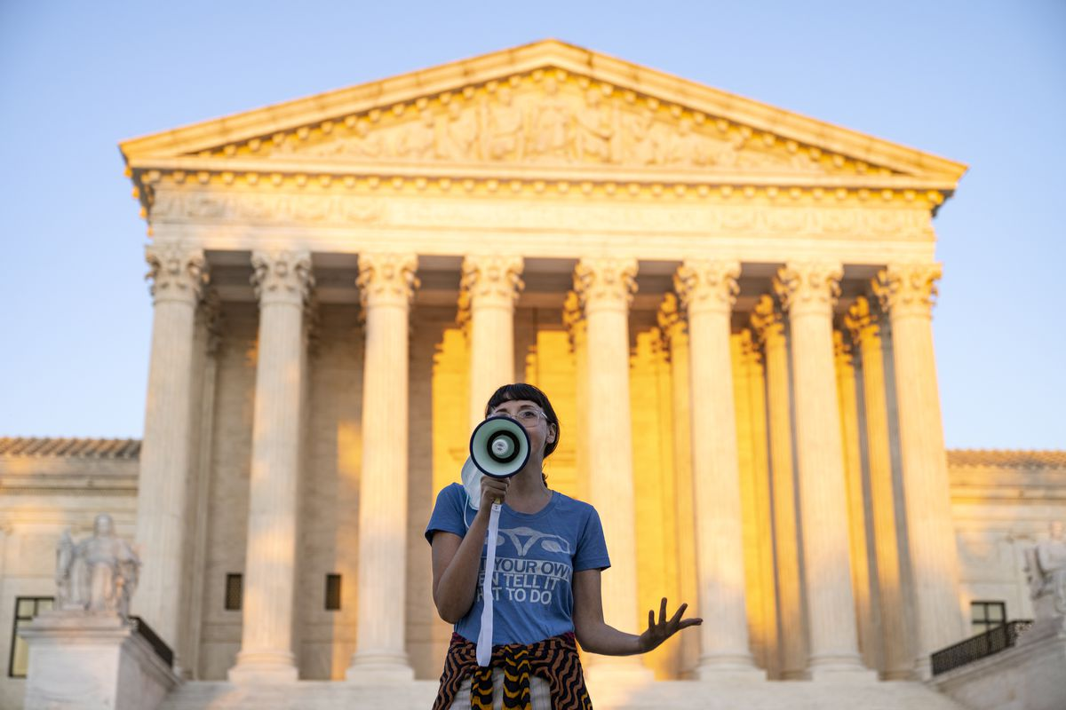 An abortion rights advocate with a bullhorn in front of the Supreme Court building.