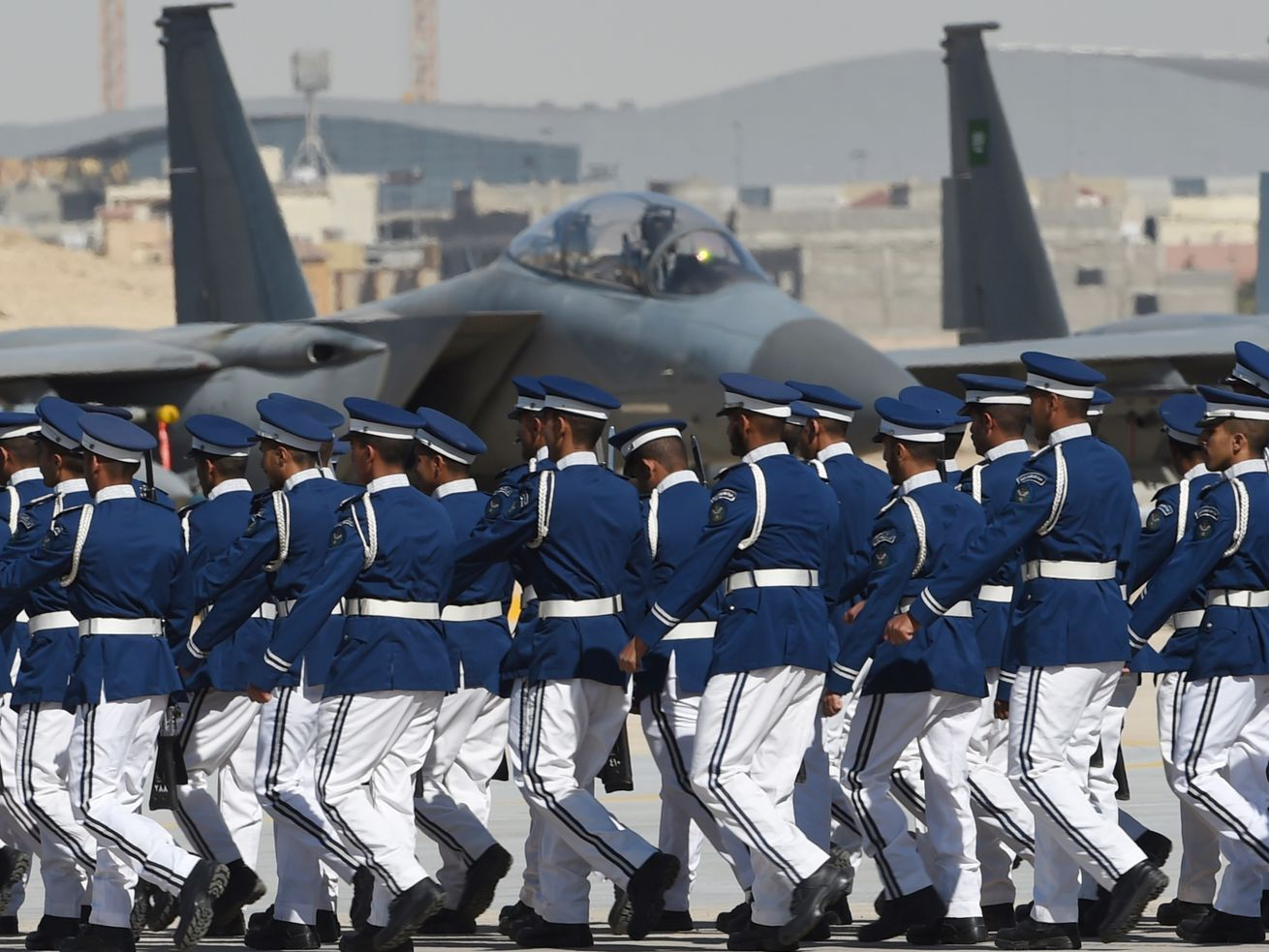Newly graduated Saudi air force officers march in front of F-15 fighter jets at King Salman airbase in Riyadh on January 25, 2017. American defense companies sell fighter jets, missiles, and other equipment to the Saudi military.