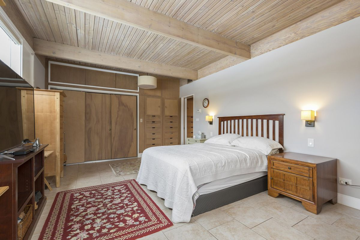 A bedroom with a wood ceilings and panels on the wall. There's a king sized bed with a wood headboard, a white blanket, and pillows.