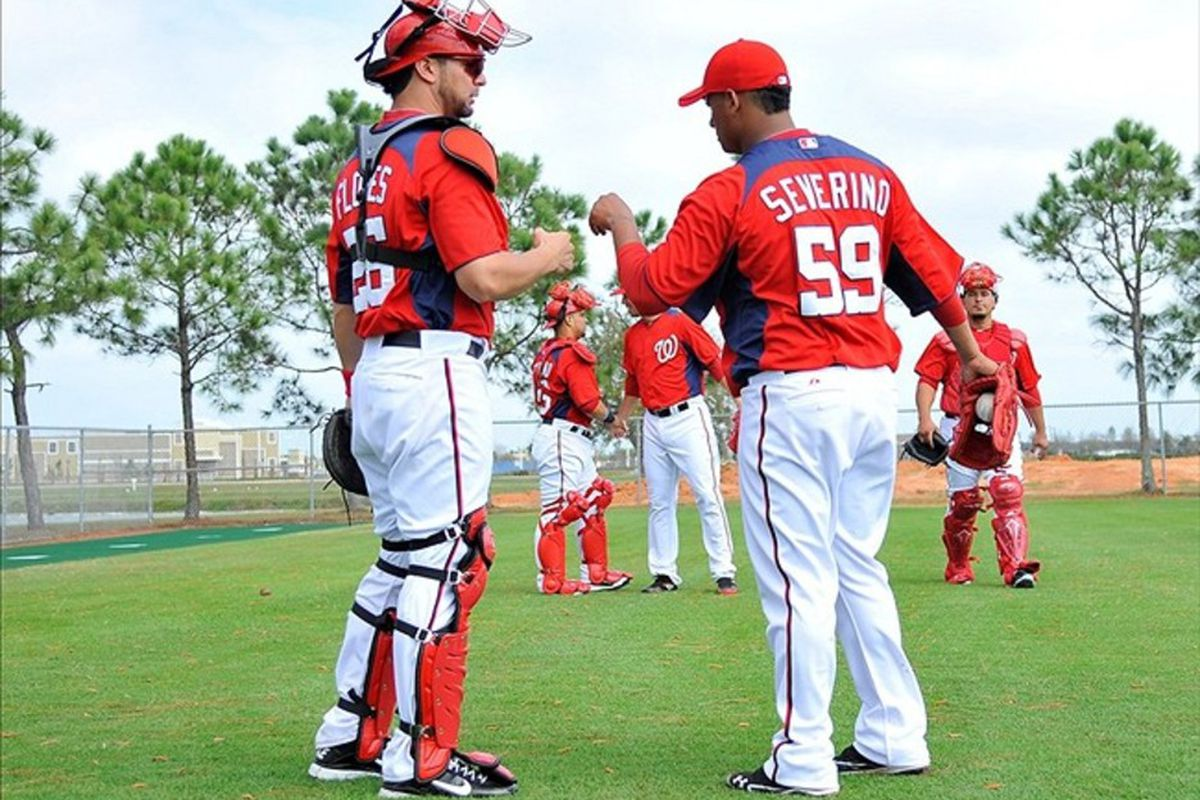 February 23, 2012; Melbourne, FL, USA;  Washington Nationals relief pitcher Atahualpa Severino (59) and catcher Jesus Flores (26) shake hands after a bullpen session at Space Coast Stadium. Mandatory Credit: Brad Barr-US PRESSWIRE