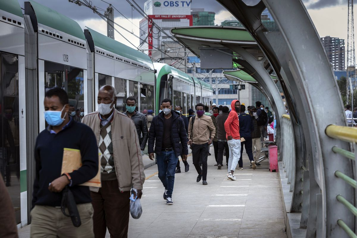Ethiopians wear masks to curb the spread of the coronavirus next to a train on the electrified Addis Ababa Light Rail transport system, in the capital Addis Ababa, Ethiopia Thursday, July 23, 2020.