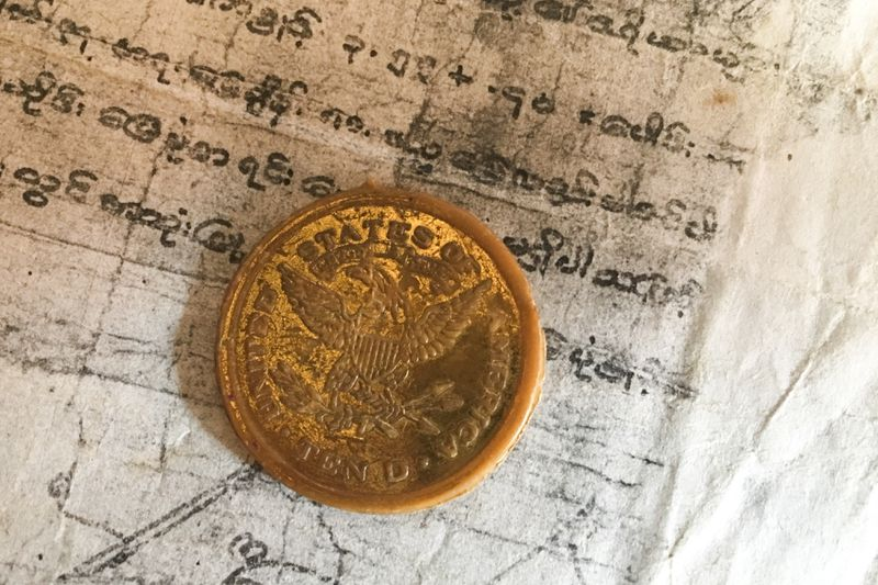 A $10 United States of America gold coin with an American eagle stamped on it, atop a document written in Burmese script.