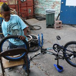 In this Tuesday, Oct. 11, 2010 photo, Jaquan Thomas, 10, fixes the tire on his bicycle at the Blackstone Bicycle Works in Chicago on Tuesday, Oct. 11, 2011. The bike shop has an after-school program where young people can earn a free bike by working at the shop for 25 hours.