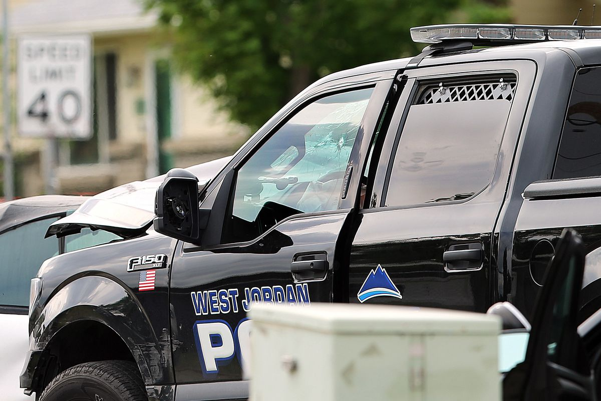 Police officers investigate after an alleged armed robber was shot dead by police after driving off with a West Jordan Patrol vehicle on Monday, May 28, 2018.