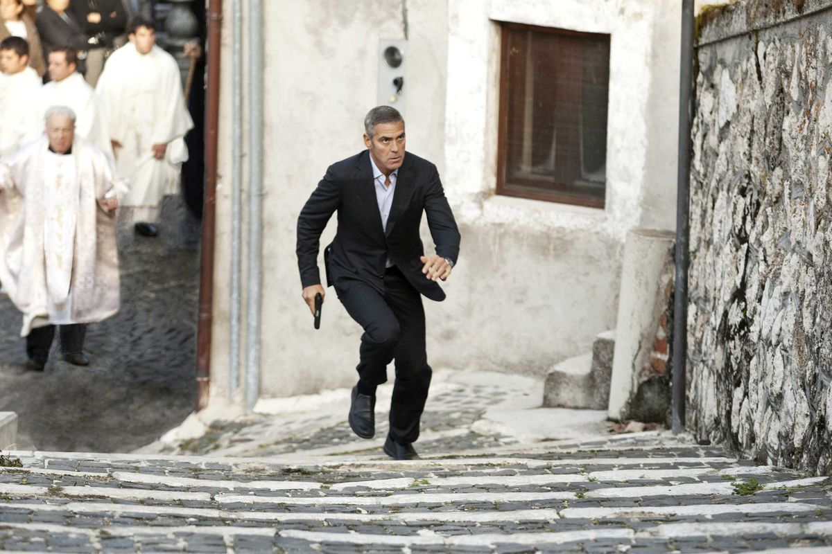 george clooney runs up stairs in rome in The American