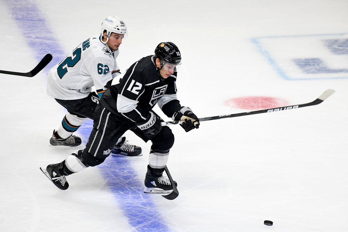 Los Angeles Kings Left Wing Trevor Moore (12) and San Jose Sharks Right Wing Kevin Labanc (62) battle for position during the second period on February 10, 2021 at the Staples Center in Los Angeles, CA.