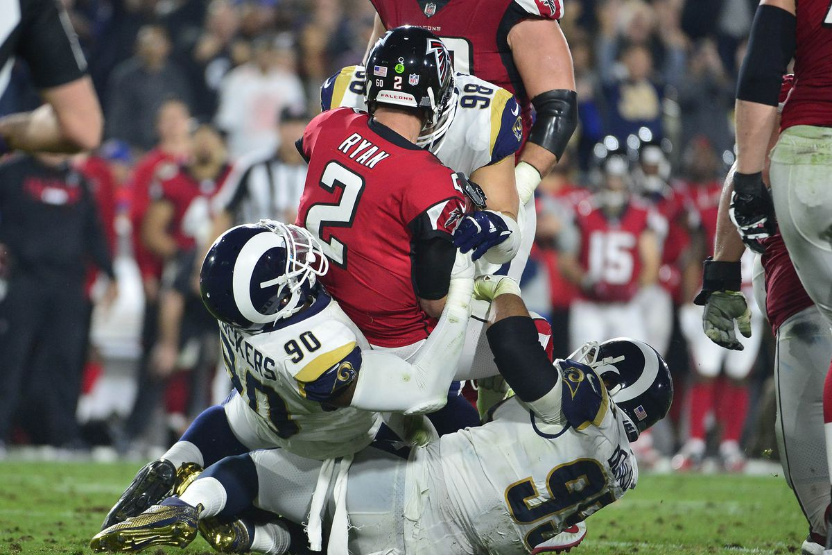 Atlanta Falcons quarterback Matt Ryan is brought down by Los Angeles Rams nose tackle Michael Brockers and defensive end Aaron Donald during the first half in the NFC Wild Card playoff football game at the Los Angeles Memorial Coliseum.