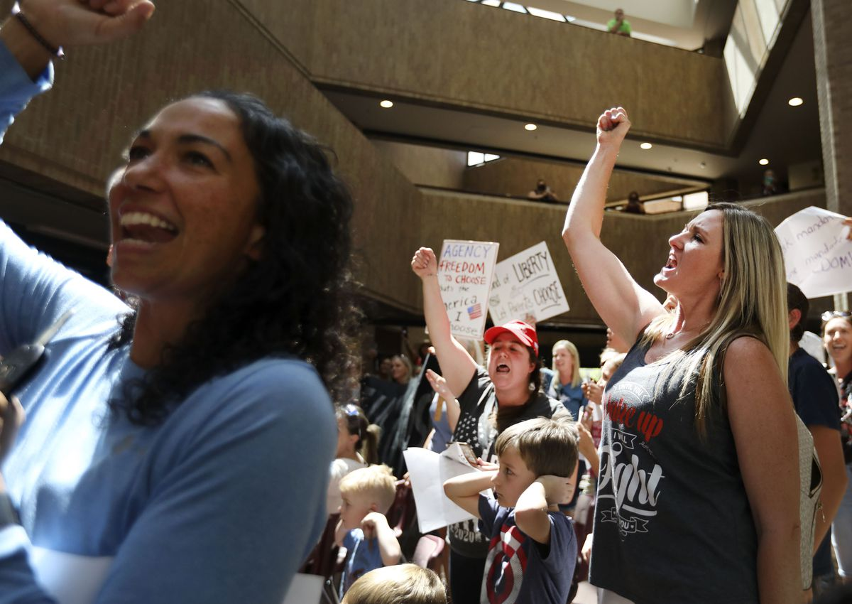 """People cheer """"freedom"""" after the Salt Lake County Council overturned the health department's """"order of restraint"""" that would have required K-6 students to wear masks when school starts during a meeting at the Salt Lake County Government Center in Salt Lake City on Thursday, Aug. 12, 2021. The proposal to overturn the order passed 6-3 along party lines, with Republicans voting to overturn the order."""
