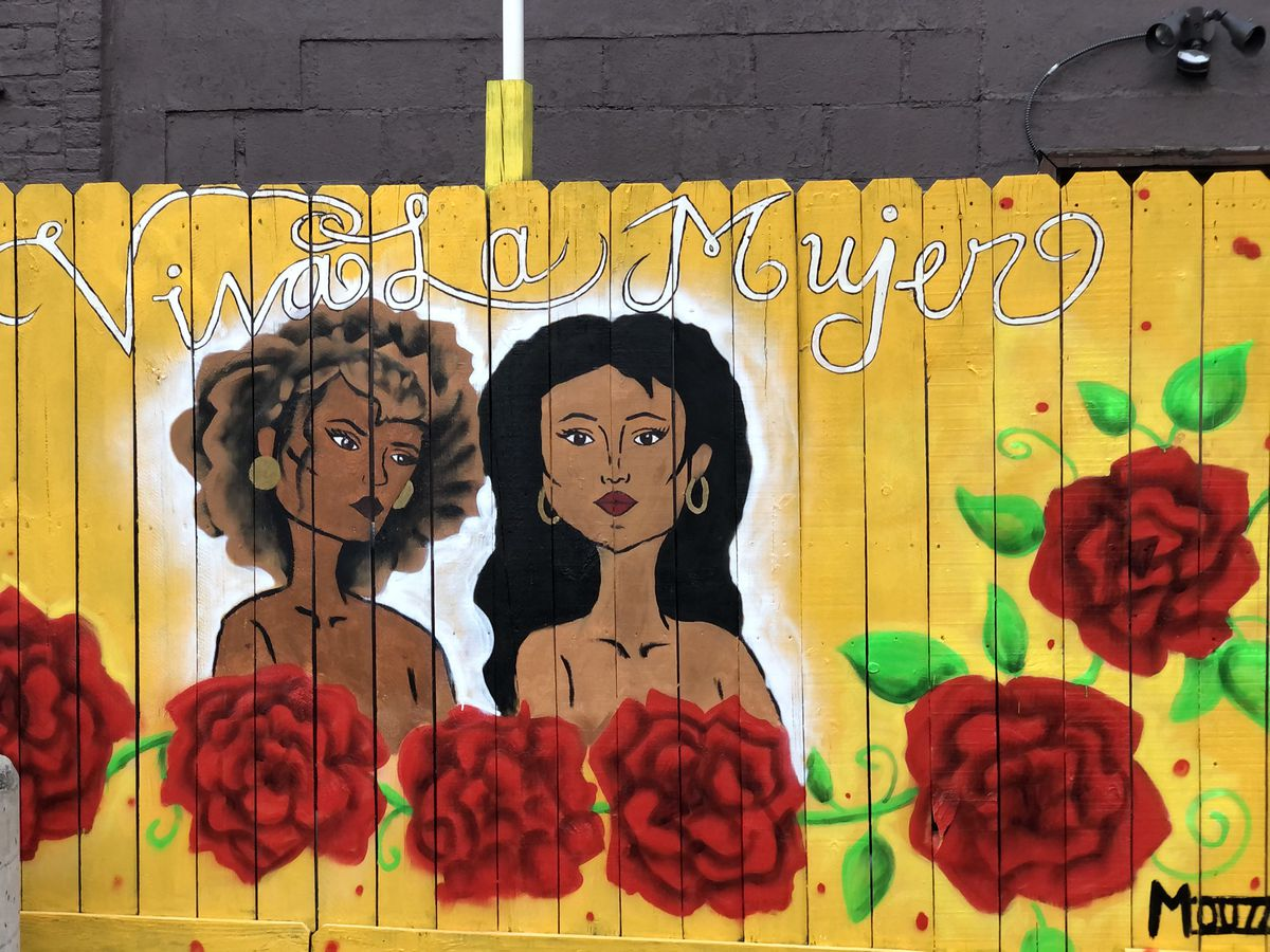 """Two Black and Brown women are set against a yellow backdrop with roses wrapping around the panel in this piece, titled """"Viva La Mujer,"""" by artist Nancy Gutierrez."""
