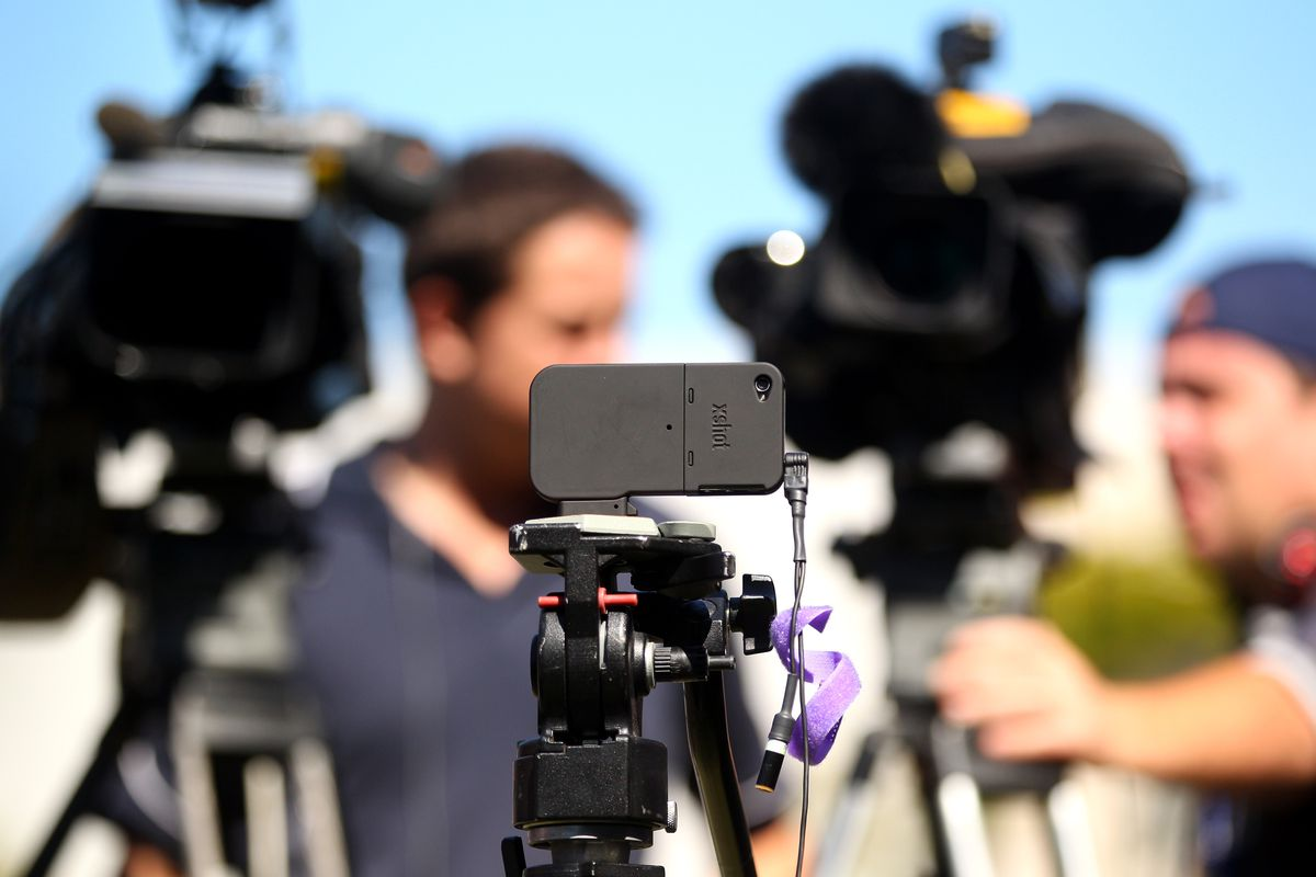 A bunch of news cameras lined up for a press conference, along with an iPhone on a tripod.